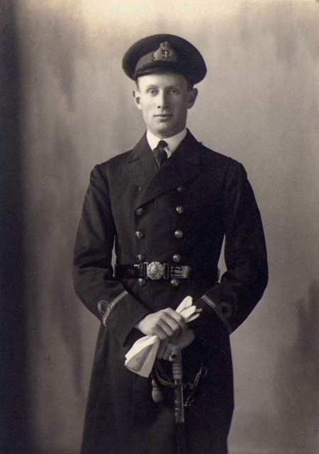 Studio portrait of Sub Lt C.G.W. Donald RN in dress uniform with sword